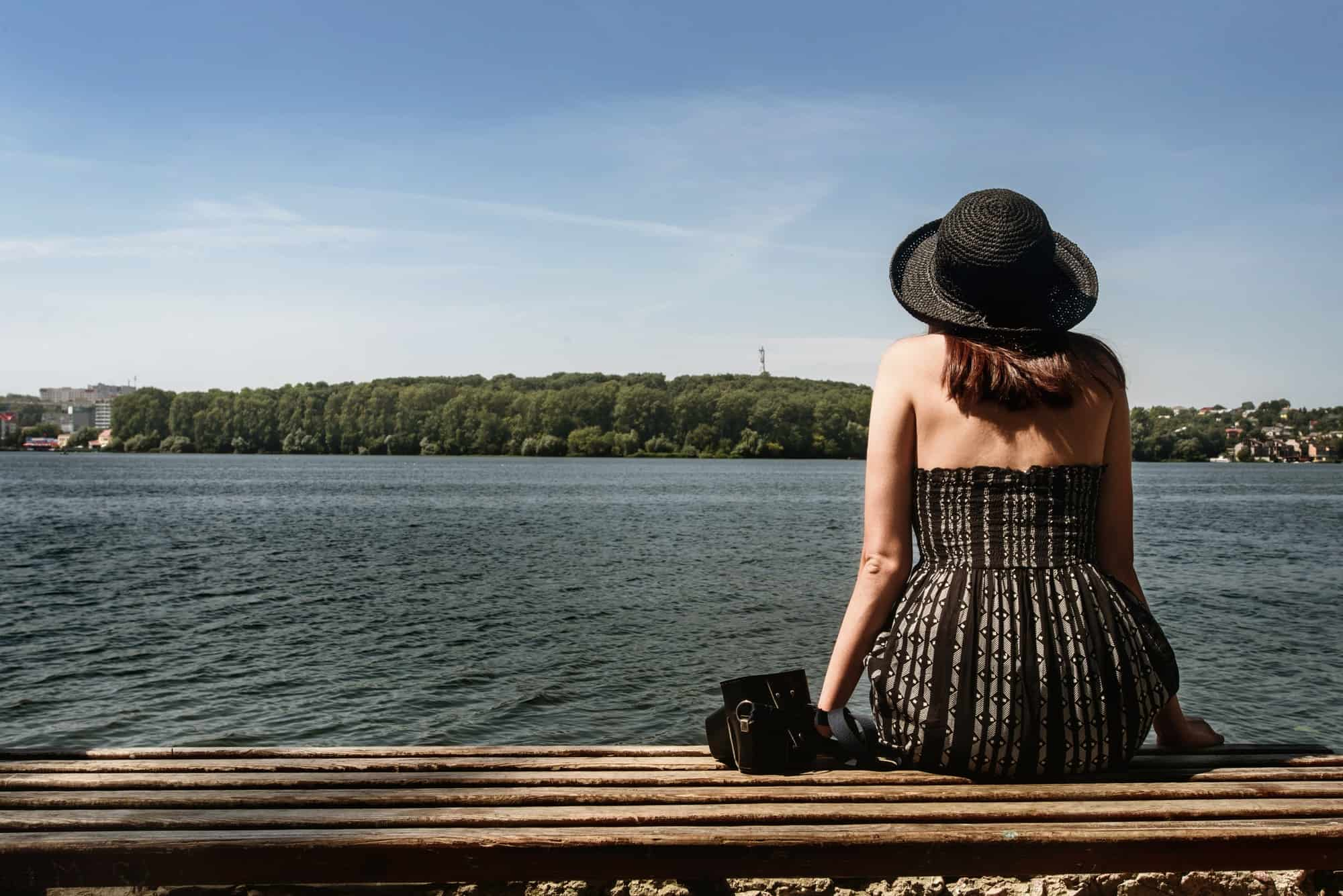 happy stylish woman hipster sitting on wooden bench at sunny shore near water